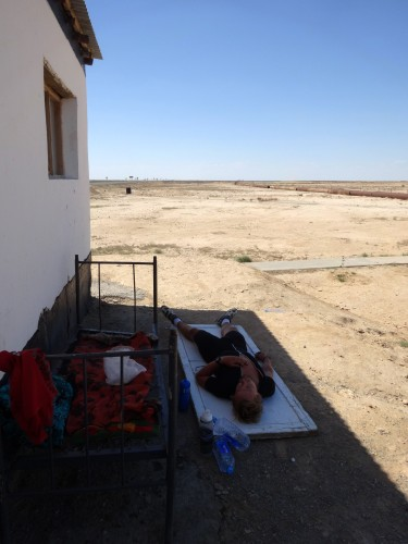 Escaping the midday sun behind a security guard's hut. Who knew sleeping on a door could be so comfortable. Near Jasliq, Uzbekistan