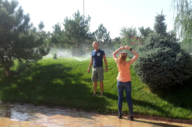Sprinklers in the middle of the day. Great way to cool down. Ana showing us the way. Tashkent, Uzbekistan.