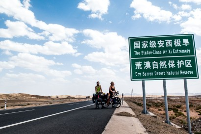"Crossing into Gansu province - they've started putting ""English"" on the signage, so we finally know where we are... The signpost describes what's going on very well. Xinjiang/Gansu Provincial border near Kumul, China."