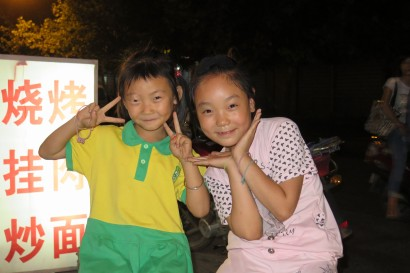 A typical evening meal surrounded by inquisitive people taking photos of us. We turned the camera back on these kids and they just started pulling funny poses and couldn't stop laughing. Baoji, Shaanxi, China.